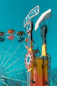 Fotografie Low angle view of ferris wheel and entertainment ride in amusement park in winter