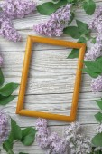 Vintage frame with lilac flowers on wooden background, spring concept
