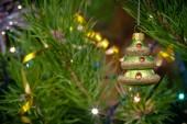 Fotografie Tree-shaped bauble hanging on festive fir tree on Christmas lights bokeh background