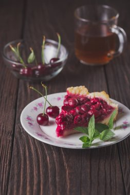 Piece of tasty cherry pie on plate on wooden table