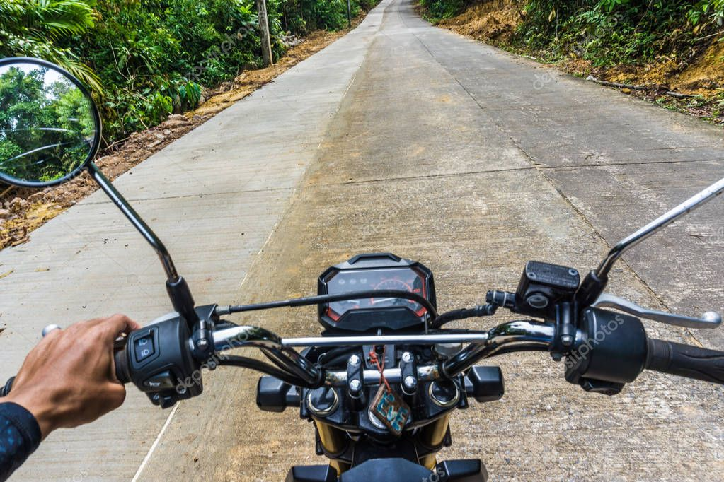 Front side of man drive motorcycle in rural country road deep forest
