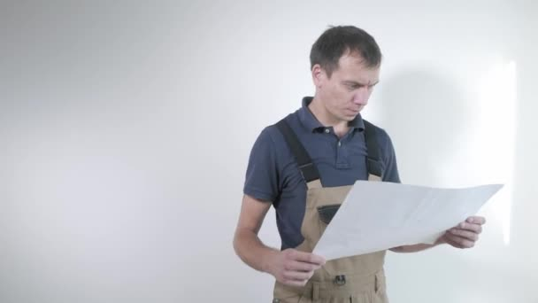 skilled handyman in brown gray jumpsuit and blue t-shirt looks at paper drawing and thinks against white wall