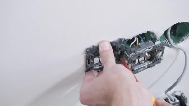 professional electrician screws switch basis into white wall with red screwdriver near hole with wires closeup