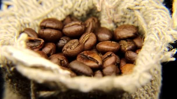 Čerstvě pražené kávové fazole v pytli hrubého prádla. Pomalu rotující kávový sáček.