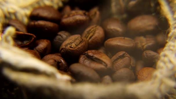 Čerstvě pražené aromatické kávové boby v pytli hrubého prádla. Z kávy se pomalu protlačí pára..