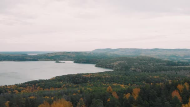 Flight over the rocks in a beautiful colorful autumn forest, among pines and lakes. drone shot, Ural, Siberia