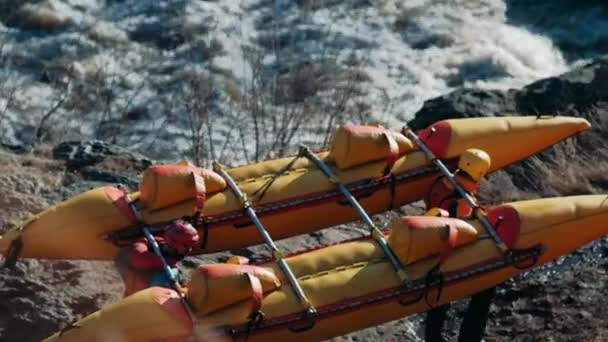 Rafting team descending raging rapids in mountain river with paddles splashing in water in slow motion. Close-up