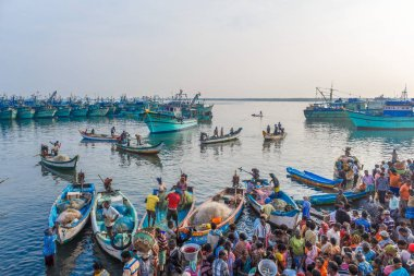 A scene at a famous fish market, where people are bargaining raw fishes placed on baskets for auction with fishing boats at seashore in the background,Kasimedu fish market,Chennai,India, Nov 20 2016