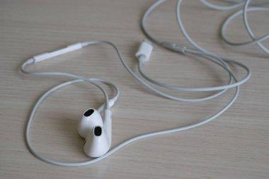 sloppy lying white headphones on white desk