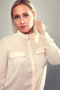 Beautiful female blonde model in shirt holding her hair