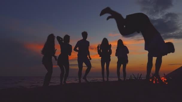 Beach party. Fiatal férfi csinál bukfenc. A háttérképet meg sziluettek.