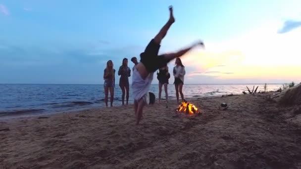 Beach party. Mladý muž dělá Salto. Siluety přátel na poza