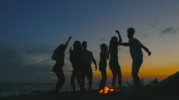 Group of people at the beach near the bonfire. Slow motion.