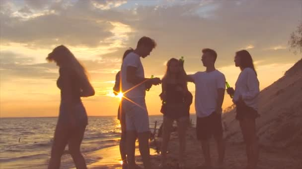 Friends near sea at sunset. Group of people enjoing good time.