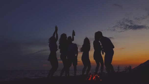 Group of people dancing at the beach near the bonfire. Slow motion.