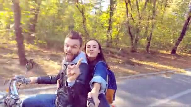 Happy couple riding a scooter in the forest. Sunny beautiful day. Selfie-stick camera view. Slow motion.