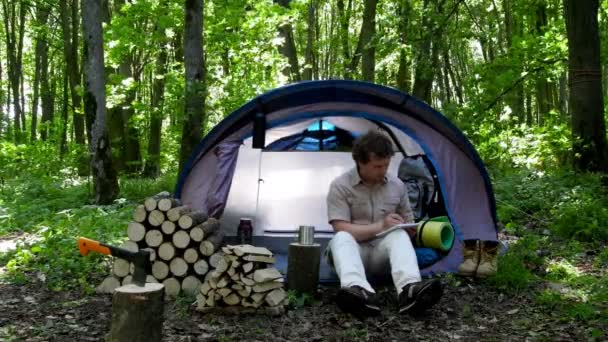Backpacker takes notes in a notebook outdoors. Campground in nature.