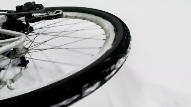 Na tomto videu můžete vidět jízdního kola. Detailní záběr kola bicyklu. Kol v zimním lese leží na jedné straně.