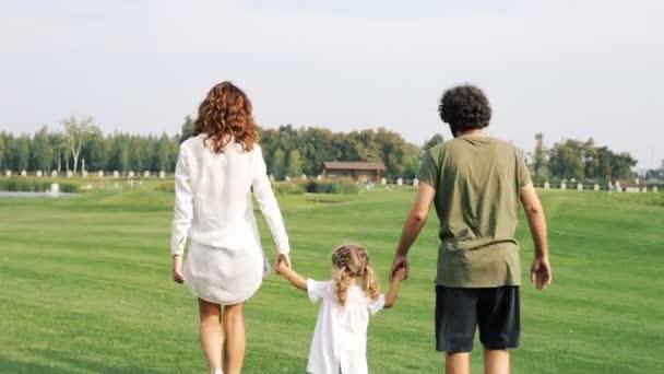 Rodina s dítětem chodí na zelený trávník v parku. Střela Steadicam.