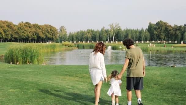 Familie mit Kind spaziert auf einer grünen Wiese im Park. Steadicam-Aufnahme.