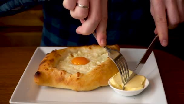 A man prepares to eat Adzhar Khachapuri in a cafe in Georgia. Vol:1. A man puts butter in Khachapuri in Adzhar and mixes it with egg and cheese. This is a traditional national dish.