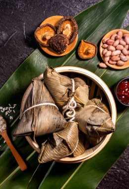 Close up, copy space, top view, flat lay. Famous asian chinese tasty handmade food in duan wu event, steamed rice dumplings shaped like pyramidal ingredient on black slate