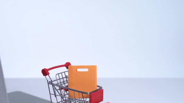 Online shopping. Mini shop cart trolley with colorful paper bags and laptop computer on white table background, buying at home concept, close up
