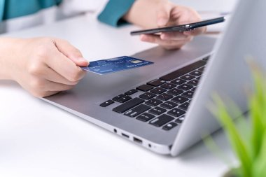 Office online paying, stay home shopping, electronic payment with credit card concept, laptop on white table background with shop cart, close up.