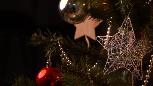 Christmas background concept- beautiful decor bauble hanging on the Christmas tree with sparkling light spot, blurry dark black background, copy space, close up, zoom in.