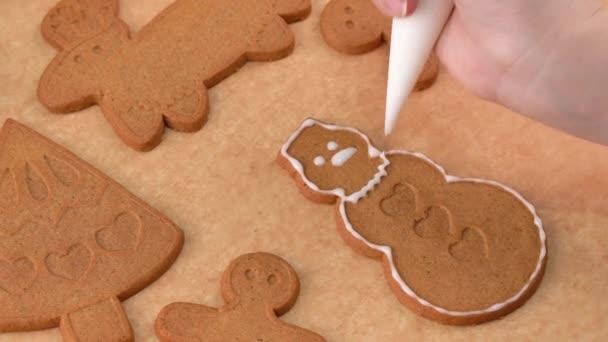 Fiatal nő díszíti karácsonyi mézeskalács House cookie-k keksz otthon cukormázas feltét a jegestáska, közelről, életmód.