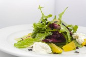 saláta görög feta sajt, narancs és fejes saláta fehér alapon egy tányéron