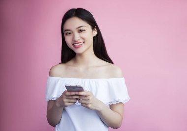 attractive smiling asian girl holding smartphone on pink background