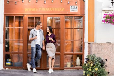 cheerful young couple holding disposable coffee cups and standing near entrance to cafe