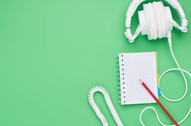 top view of the table of a teenage child, composition headphones notebook pencil on light green background