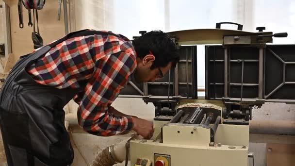 Arbeitsprozess in der Tischlerei. Ein Mann in Overalls benutzt eine Hobelmaschine in einer Tischlerei. Beruf, Tischlerei, Holzbearbeitung und Personenkonzept