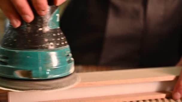 Arbeitsprozess in der Tischlerei. Ein Mann verwendet Elektroschleifer für Holz in einer Tischlerei. Beruf, Tischlerei, Holzbearbeitung und Personenkonzept