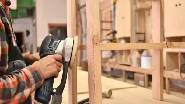 Arbeitsprozess in der Schreinerei. Ein Mann verwendet Elektroschleifer für Holz in einer Schreinerei. Beruf, Schreinerei, Holzbearbeitung und Personenkonzept