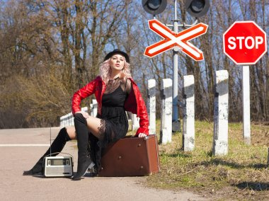 Happy beautiful traveling woman with retro suitcase on the road. The concept of tourism.