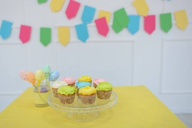 Beautiful multi-colored cupcakes. The room is decorated with bright decor. Close-up.