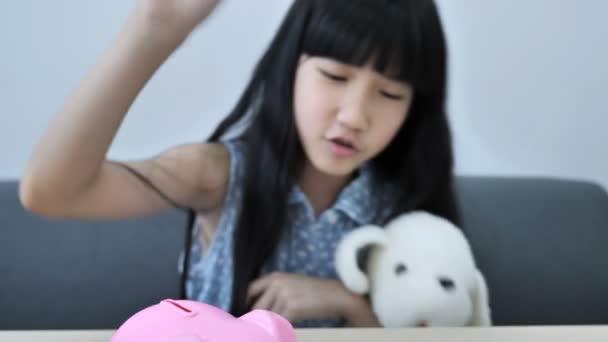 4k kleines asiatisches Mädchen legt Geldmünze in Sparschwein auf Holztisch, außer für die Zukunft.