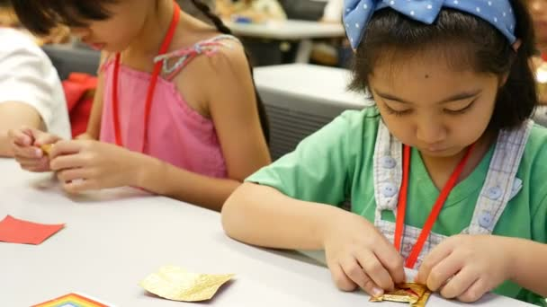 4K : Asian child learning to folding Japanese paper origami, art of paper folding, which is often associated with Japanese culture.