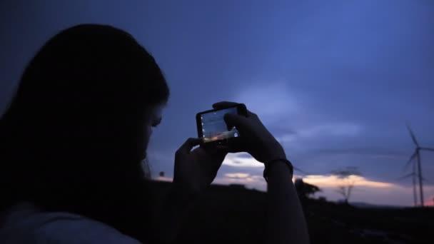 4k Tourist fotografiert Sonnenuntergang in Windkraftanlage Stromgenerator bei Sonnenuntergang