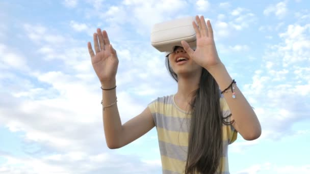 Slow motion 4K of Asian girl having fun with virtual reality glasses while standing over the sky