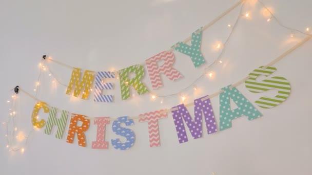 4k barevné Vánoce příznaky, visí na zdi s girlandami z lucerny jako slavnostní dekorace pro oslavy