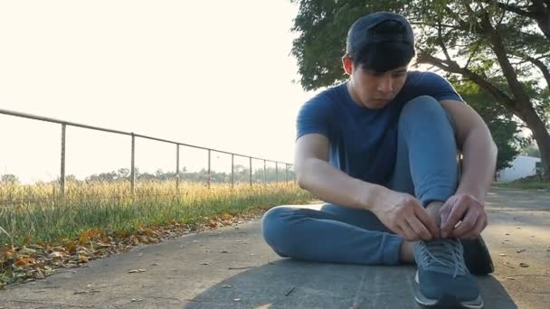 Young Asian man putting on pair of shoes, Tie the laces on the shoes, Slow motion