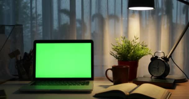 Laptop-val zöld képernyő. Sötét office. Dolly, balról jobbra. Tökéletes, hogy a saját kép vagy videó.