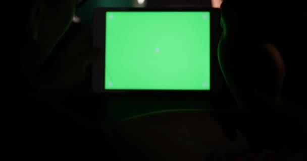 Přes rameno pohled psaní a sledování na počítači. Zelená obrazovka technologie používány. Chroma klíč laptop.