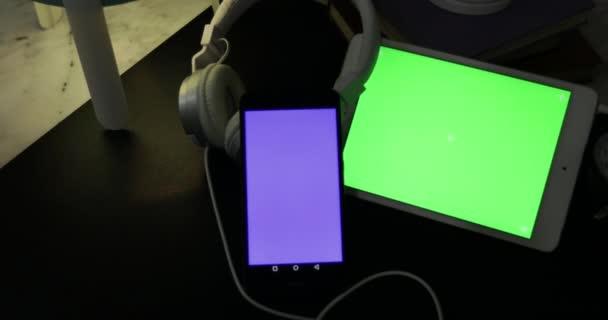 Dolly střílet zelené obrazovky na tabletu Digital a sluchátka na stole v noci