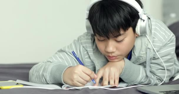 Young asian teenage student listen to music and doing homework at home,Dolly shoot.