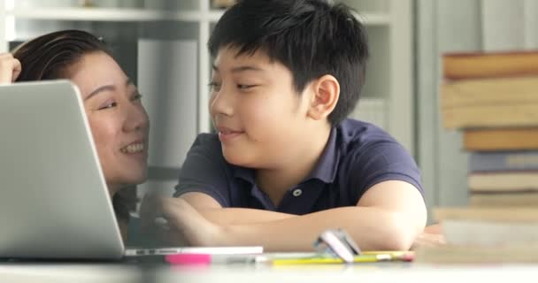 Cute asian mother helping your son doing your homework at home with smile face together.